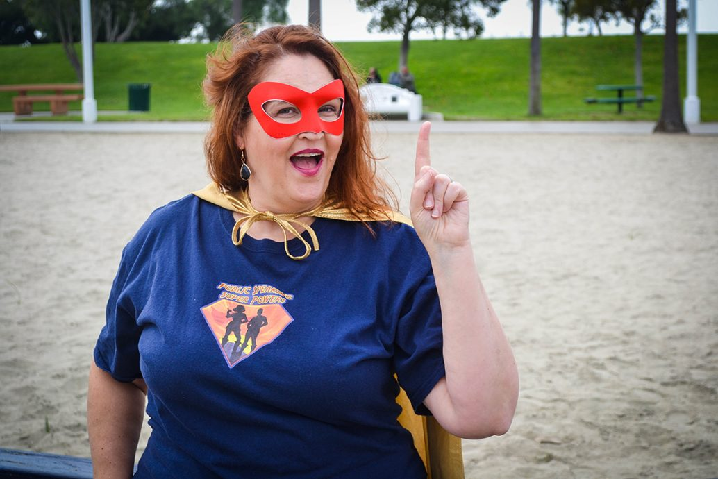 Carma Spence in a superhero costume with an aha gesture
