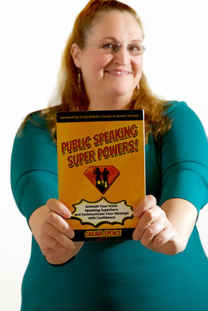 Carma Spence holding a copy of Public Speaking Super Powers
